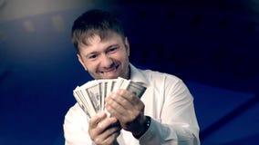 Den unga mannen som rymmer en stor mängd pengar i hans händer, kan inte tro att han rymmer den lager videofilmer