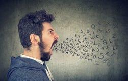 Den unga mannen som skriker med alfabet, märker flyg ut ur mun royaltyfri fotografi
