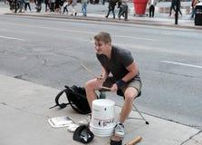 Den unga mannen som spelar provisoriet, trummar på några tomma målarfärghinkar fotografering för bildbyråer