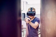 Den unga mannen som spelar skytte, spelar i virtuell verklighethörlurar med mikrofon på den stads- byggnadsbakgrunden utomhus Tek Royaltyfri Foto
