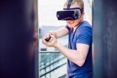 Den unga mannen som spelar skytte, spelar i virtuell verklighethörlurar med mikrofon på den stads- byggnadsbakgrunden utomhus Tek Arkivbilder