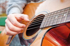 Den unga mannen som spelar slut för akustisk gitarr upp det fria i höst, parkerar Arkivfoton