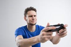 Den unga mannen som spelar videospel i svart skjorta, isolerade studion Royaltyfri Foto
