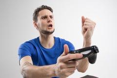 Den unga mannen som spelar videospel i svart skjorta, isolerade studion Arkivbild