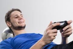 Den unga mannen som spelar videospel i svart skjorta, isolerade studion Arkivfoto