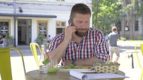 Den unga mannen som talar vid smartphonen, under lunch, glidaren sköt vänstert stock video