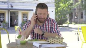 Den unga mannen som talar vid smartphonen, under lunch, glidaren sköt vänstert arkivfilmer