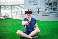 Den unga mannen som trycker på kontrollbordknappen som tycker om virtuell verklighetexponeringsglas, eller anblickar 3d i staden  Arkivbilder