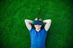 Den unga mannen som tycker om virtuell verklighetexponeringsglashörlurar med mikrofon, eller anblickar som 3d ligger på den gröna Arkivbild