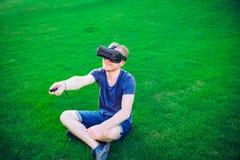 Den unga mannen som tycker om virtuell verklighetexponeringsglashörlurar med mikrofon, eller anblickar som 3d sitter på den gröna Arkivbild