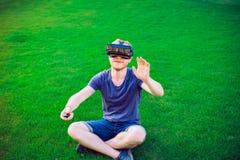 Den unga mannen som tycker om virtuell verklighetexponeringsglashörlurar med mikrofon, eller anblickar som 3d sitter på den gröna Arkivbilder