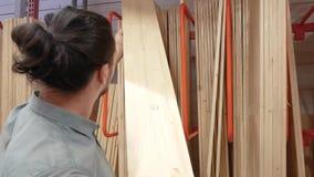 Den unga mannen som väljer trä, stiger ombord i ett maskinvarulager eller lager arkivfilmer