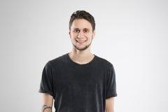 Den unga mannen som var lycklig i svart skjorta, isolerade studion Arkivfoton