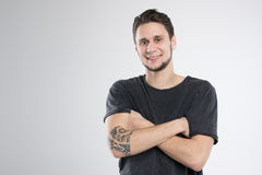 Den unga mannen som var lycklig i svart skjorta, isolerade studion Arkivfoto