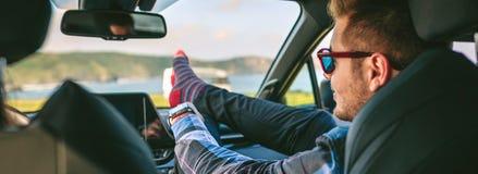 Den unga mannen som vilar fot, up sammanträde på bilen fotografering för bildbyråer