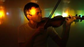 Den unga mannen spelar fiolen i nattklubb lager videofilmer