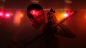 Den unga mannen spelar fiolen i nattklubb stock video