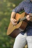Den unga mannen spelar på hans gitarr Arkivfoto
