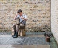 Den unga mannen spelar sågen på den södra banken, London Arkivfoto