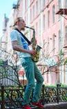 Den unga mannen spelar saxofonen Royaltyfria Bilder