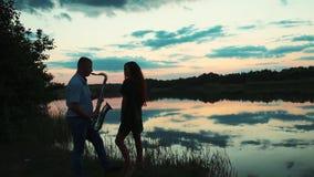 Den unga mannen spelar saxofonen för flicka på solnedgången stock video