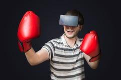 Den unga mannen spelar videospelet och boxas med exponeringsglas för virtuell verklighet 3D Royaltyfria Bilder