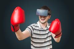 Den unga mannen spelar videospelet och boxas med hörlurar med mikrofon för virtuell verklighet 3D Royaltyfri Foto