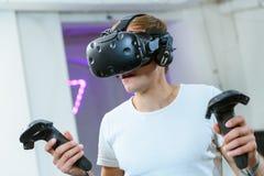 Den unga mannen spelar VR-lekar royaltyfri fotografi