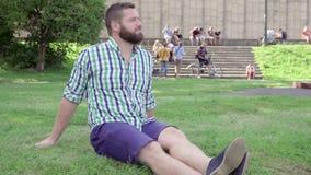 Den unga mannen stänger bärbara datorn och kopplar av och att sitta på gräs steadicam lager videofilmer
