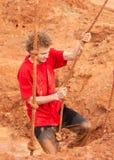 Den unga mannen stänkte ned med gyttjaklättring ut ur en grop genom att använda ett rep under en kurs för gyttjakörningshinder royaltyfria bilder