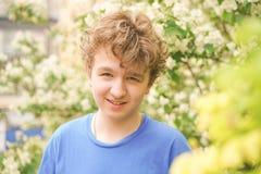 Den unga mannen står bland blommorna och tycker om sommar och att blomma arkivbilder