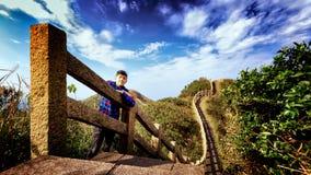 Den unga mannen står bredvid fotbanan av att bölja trappa arkivfoton