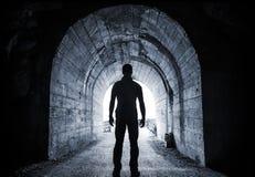 Den unga mannen står i mörk tunnel Arkivfoton