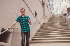 Den unga mannen står på den stora trappan royaltyfri fotografi