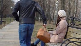 Den unga mannen stjäler en påse för kvinna` s från en bänk i parkera royaltyfri foto