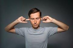 Den unga mannen stoppade hans öron med fingrar royaltyfri foto