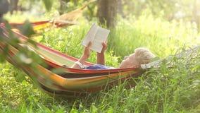 Den unga mannen svänger att ligga i hängmattan och läser en bok under siesta lager videofilmer