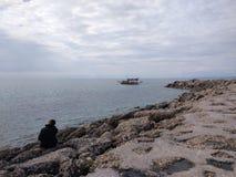 Den unga mannen tänker i en sjö royaltyfri foto