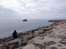 Den unga mannen tänker i en sjö royaltyfri fotografi
