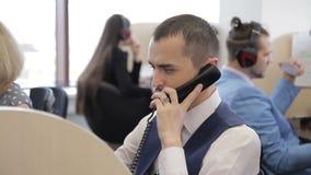 Den unga mannen talar på telefonen bland anställda i appellmitt lager videofilmer