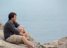 Den unga mannen tanke-vaggar in kusten Royaltyfria Foton