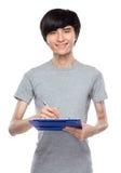 Den unga mannen tar anmärkningen på skrivplattan Arkivbild