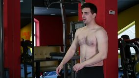 Den unga mannen tar av skjortan på idrottshallen arkivfilmer