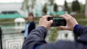 Den unga mannen tar bilder av flickan på smartphonen lager videofilmer