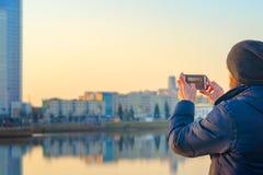 Den unga mannen tar bilder av staden på en smartphone Fotografering för Bildbyråer