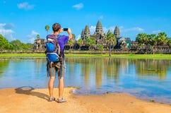 Den unga mannen tar ett foto av den Angkor Wat templet Arkivfoto