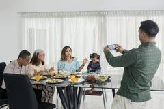 Den unga mannen tar fotoet hans familj i äta middag tabell royaltyfria foton