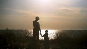 Den unga mannen tar handen av lite pojken på stranden på solnedgången konturfader och hans son som ser seascapen Begreppsfa