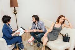 Den unga mannen tar med doktorn Terapeuten rymmer en handteckning och ser grabben Den unga kvinnan är i förtvivlan henne Royaltyfria Foton