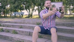 Den unga mannen tar selfie av minnestavlan som sitter på trappa arkivfilmer